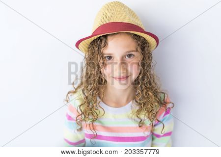 A Portrait of 9 years old girl with curly hair, isolated on gray