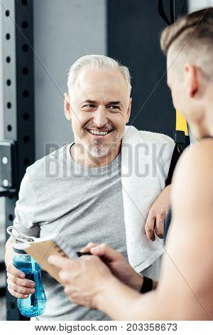 Senior Sportsman Talking With Trainer