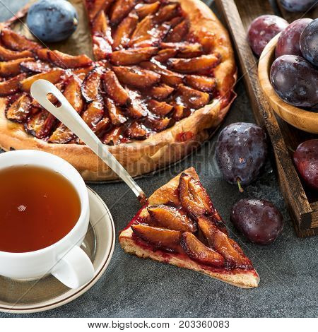 Homemade plum pie and cup of tea autumn dessert with fresh plums baking healthy vegetarian food square image