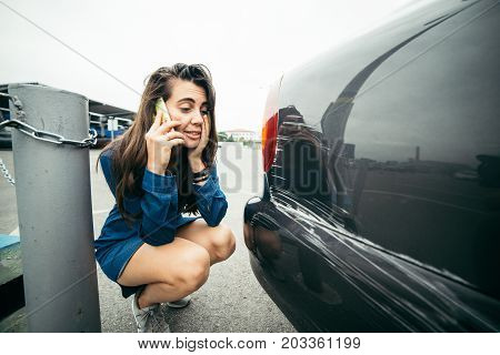 sad woman standing near car with scratch on parking and talking by the phone