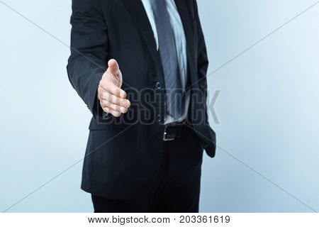 Nice to meet you. Nice pleasant good looking man standing against blue background and showing his hand while greeting a person