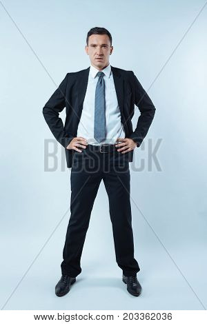 Confident look. Smart nice good looking man standing against blue background and giving you a confident look while being a professional businessman