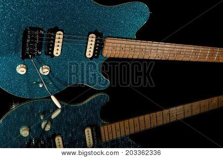 Glam rock guitar. Electric guitar with vibrant blue glitter finish. Fun party band musical instrument with funky look.