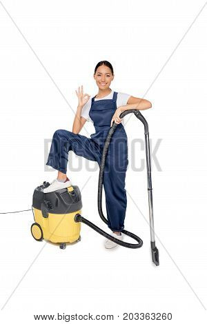 cheerful asian cleaner with vacuum cleaner showing ok sign while looking at camera isolated on white