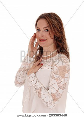 A beautiful young woman in a lace blouse and brunette hair standing in profile and smiling isolated for white background