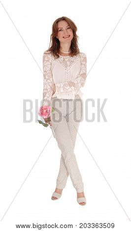 A beautiful young Caucasian woman in a lace blouse and brunette hair holding a pink rose in her hand isolated for white background