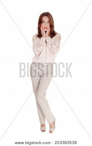 A beautiful young woman in a lace blouse and brunette hair standing in dress pants with hands on her face isolated for white background