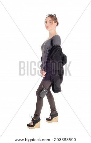 A slim young woman in gray t-shirt with her jacket on her arms looking serious is ready for a walk isolated for white background