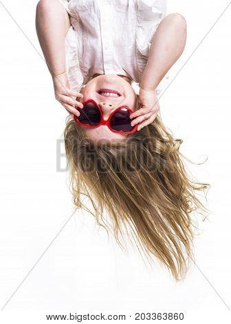 A Little girl with glasses upside down head