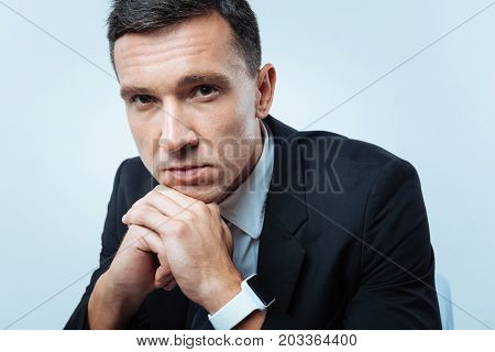 Thoughtful look. Handsome nice serious entrepreneur holding his chin and looking at you while sitting against blue background