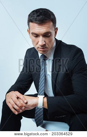 What time is it. Serious nice busy businessman looking at the watch and checking the time while sitting against the blue background