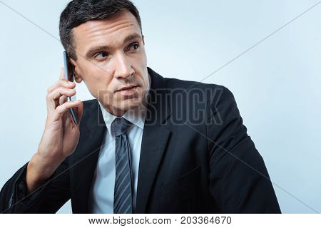 In touch. Serious handsome pleasant man holding a cell phone and listening to his interlocutor while having a phone conversation