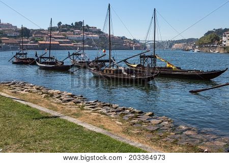 Typical Rabelo Boats on the Bank of the Douro River and Vila Nova de Gaia in background - Porto Portugal