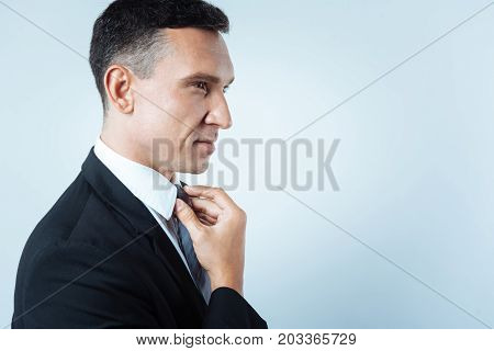 Formal style. Pleasant cheerful nice businessman touching his tie and fixing it while getting ready for work