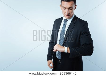 What time is it. Confident busy handsome looking at his watch and checking the time while having an appointment