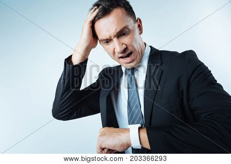 How late. Unhappy stressed handsome man holding his head and checking the time while being late for his appointment