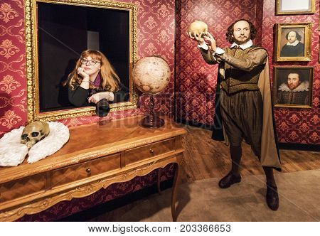 Berlin - March 2017: a girl with  Shakespeare wax figure in Madame Tussaud's museum