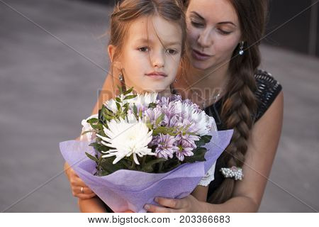 Young beautiful mother escorts her daughter to the first class. The first of September is the day of knowledge
