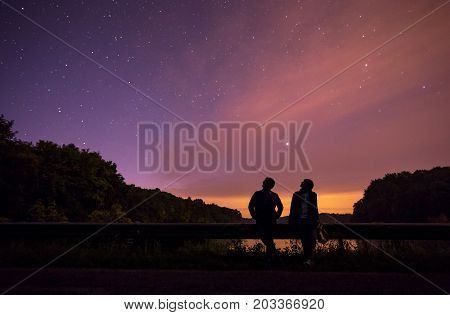 Two People Looking At The Stars, Backlight, The Starry Sky Through The Clouds Bump Highway