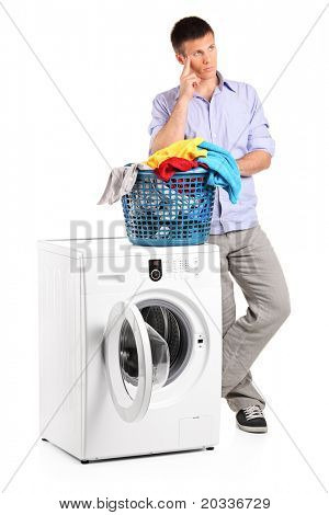 Thoughtful young man posing next to a washing machine isolated on white background