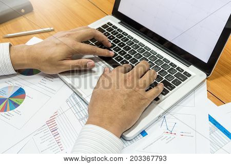 Businessman working with laptop and documents in office