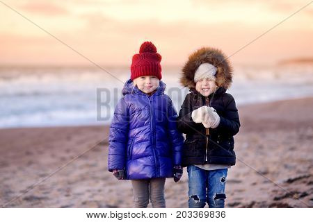 Two cute little sisters having fun together at winter beach on cold winter day. Kids playing by the ocean. Winter activities for children.