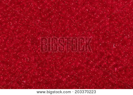 Seed beads of red color on the textile background close up