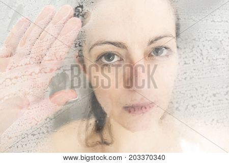 A Stressed woman leaning on weeping glass shower door