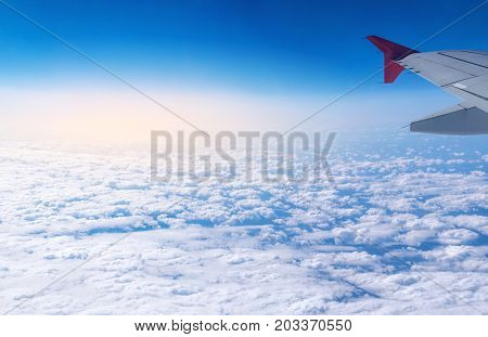 Wing Of Airplane In Flight On A Background Of Clouds. Concept Of Travel And Flights To New Countries