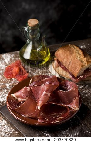 a plate with some slices of serrano ham on a rustic wooden table, next to a cruet with olive oil and a sandwich of typical catalan pa amb tomaquet, bread with tomato, stuffed with serrano ham