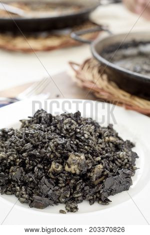 closeup of a plate with spanish arroz negro or black paella, made with squid ink, on a table set for lunch, next to some paelleras, the paella pans where this typical dish is cooked and served