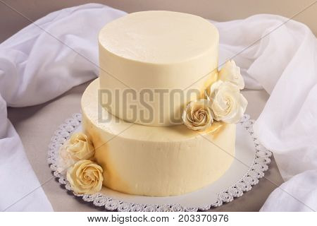 Beige 2 Tiered Wedding Cake Decorated With Mastic Roses Stands On Fabric Background
