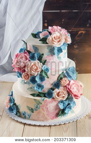 A Beautiful Home Wedding Three-tiered Cake Decorated With Pink Roses And Blue Flowers In A Rustic St