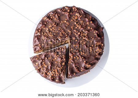 Isolated Chocolate Layered Cake With Nougat And Sponge Cake In The Cut On The Plate, Top View