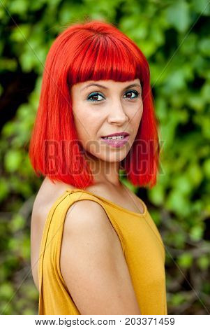 Happy red hair woman with yellow dress in a park