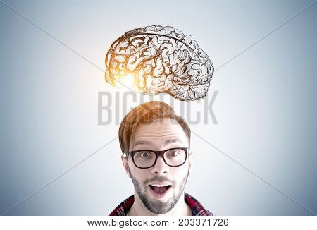 Close up of an astonished young man wearing glasses and standing with an open mouth near a gray wall with a brain sketch drawn on it. Toned image