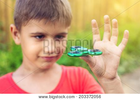 A Boy Plays With Spinner Twisting It In His Hand On Outdoors. Trends In Children's Anti-stress Toys