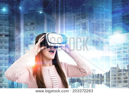 Close up portrait of a young woman wearing a pink cardigan and VR glasses. She is amazed by what she is seeing. She is standing against a night city background. Toned image double exposure