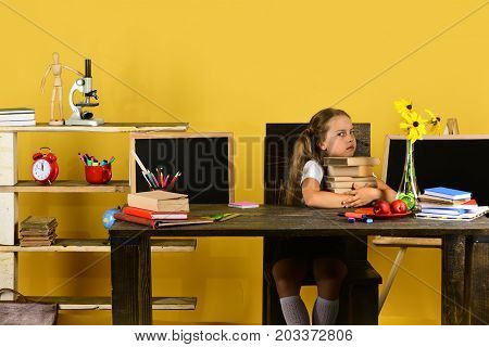 Schoolgirl With Grumpy Face Holds Books Stack