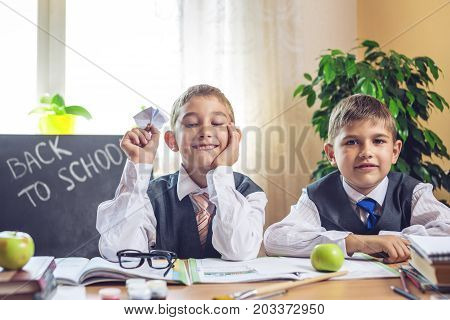 Back To School. Cute Children Sitting At The Desk In The Classroom. Boys Is Acting Up Throwing A Pap