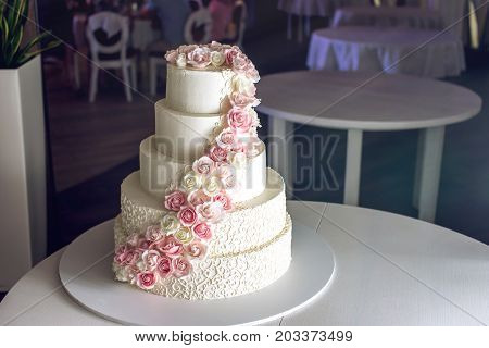 A Large Tiered Wedding Cake Decorated With Pink Roses On The Table In The Restaurant