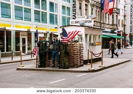 BERLIN - MARCH 27, 2014: Tourist taking photo with men dressed as American soldiers in front the Checkpoint Charlie in Berlin, Germany. Crossing point between East and West Berlin during the Cold War.