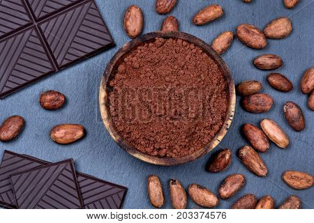 Cacao powder in a bowl with chocolate and cacao beans on slate closeup