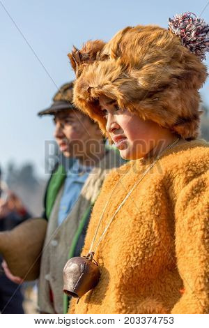 PERNIK, BULGARIA - JANUARY 27, 2017: Boy dressed in brown bear-like fur costume is taking part of ritual at Surva, International Festival of the Masquerade Games