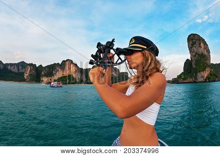 Young captain woman in cap on deck of sailing yacht taking sight in sextant to measure boat altitude position in tropical sea on summer cruise. Travel adventure yachting with kids on family vacation. poster