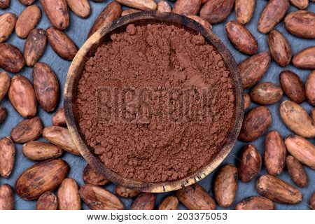 Cacao powder in a bowl with beans on slate closeup
