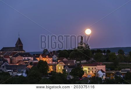 The statue of Pope Urbanus 2 in the Champagne village of Chatillon-sur-Marne in the Champagne district in France rising of the moon.