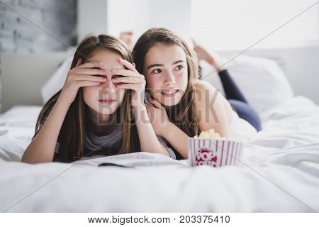 scared friends or teenage girls eating popcorn and watching horror movie on tv at home