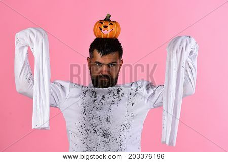 Halloween, Culture And Traditions Concept. Guy With Beard Holds Pumpkin