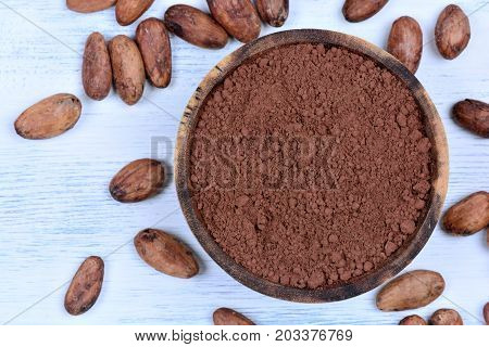 Cacao powder in a bowl and beans on wooden table